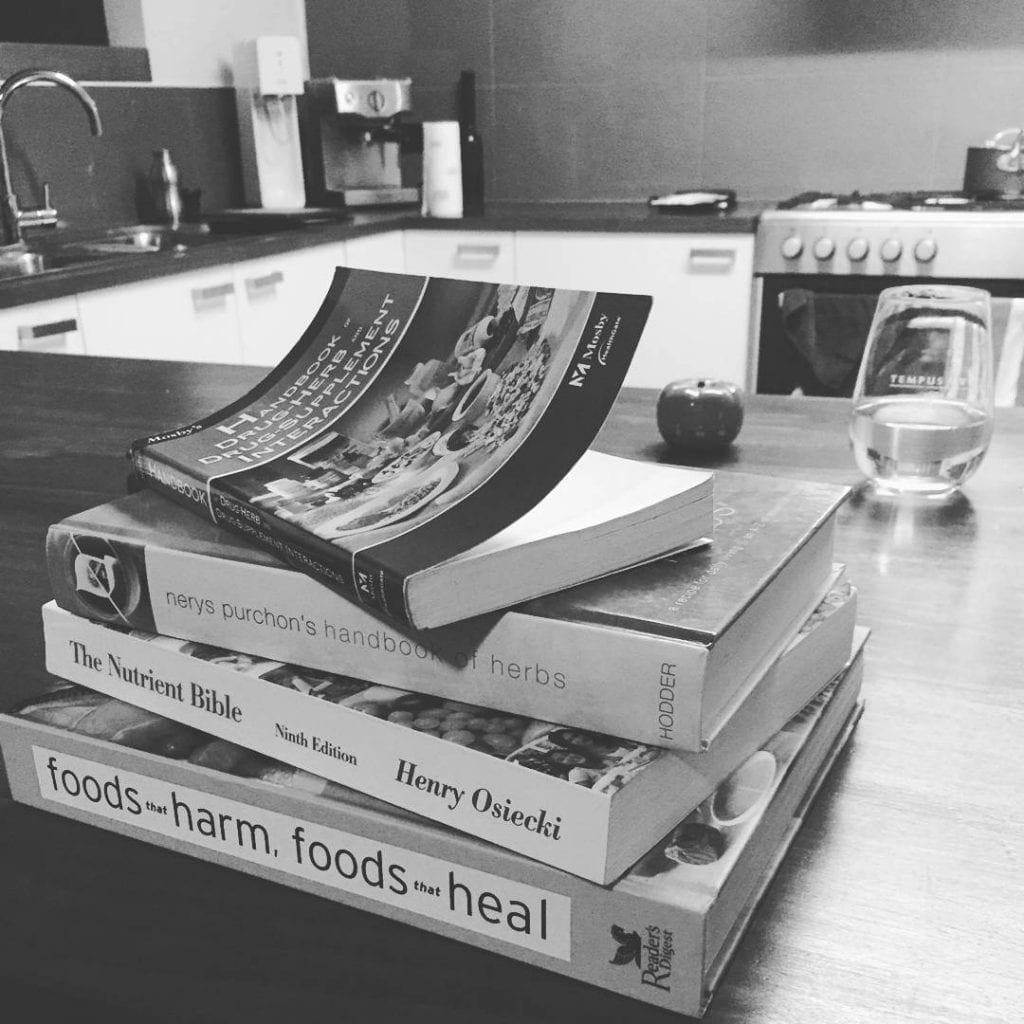 a stack of nutritional books on the kitchen table